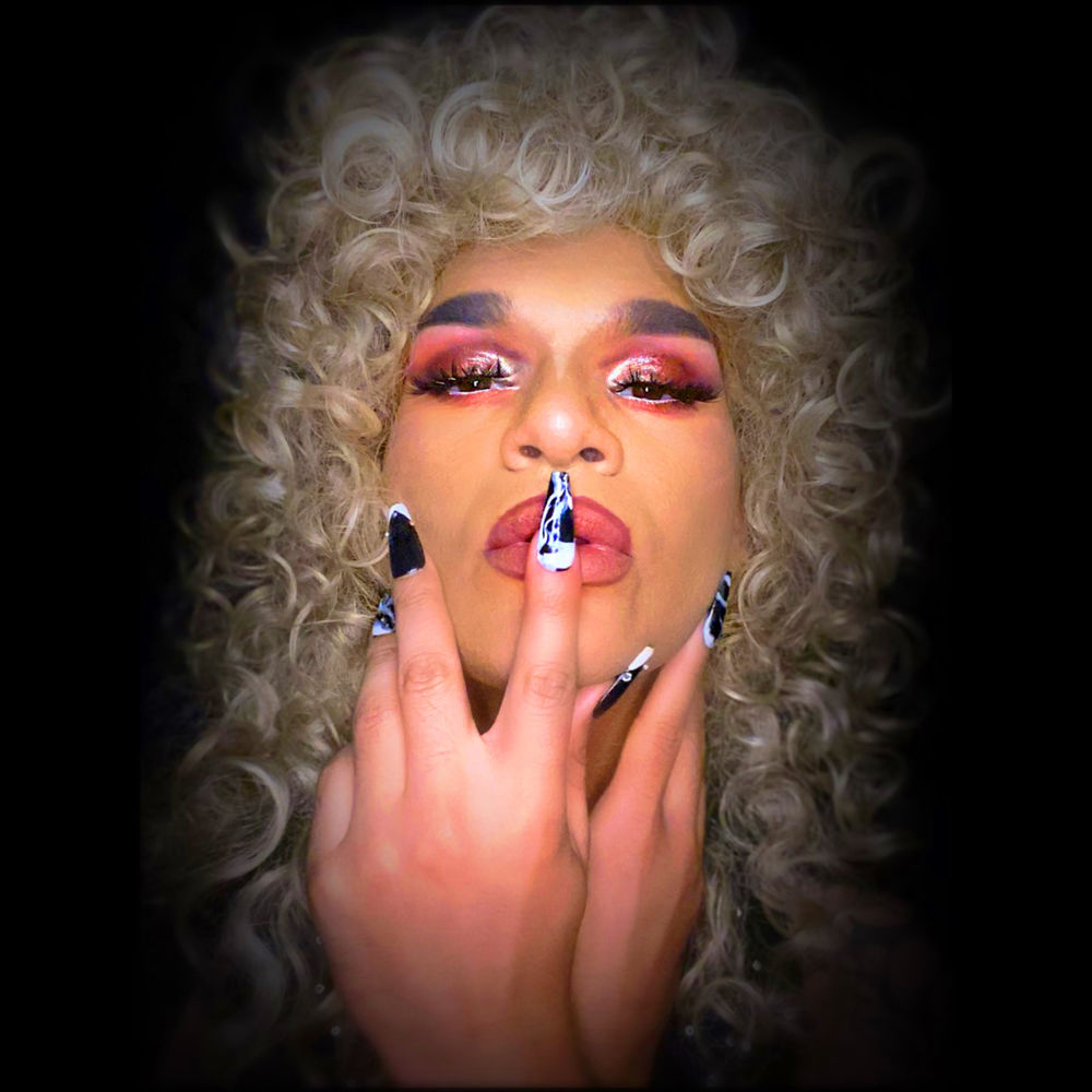 A closeup shot of a drag queen with fair colored skin, blonde curly hair, pink eyeshadow and lipstick, and black and blue long nails