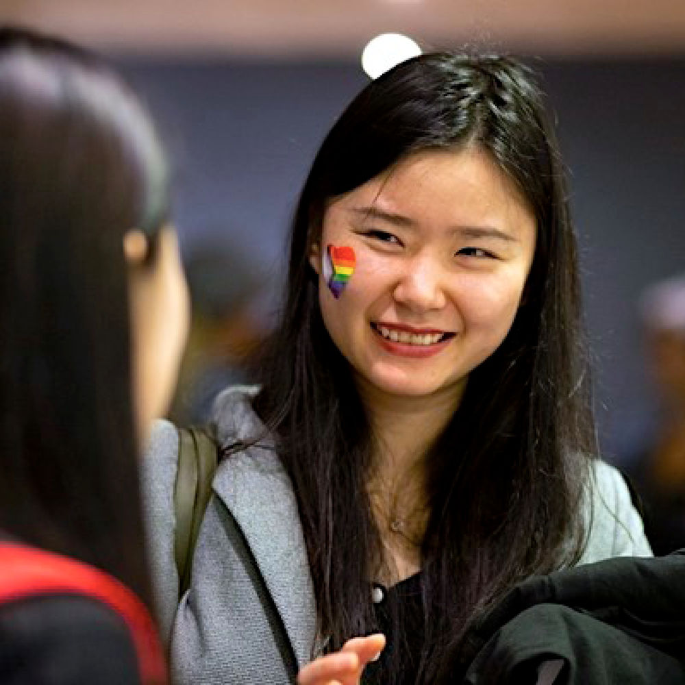 Two temple Students at an Institutional Diversity LGBTQIA + event. One is smiling and has a heart sticker on her right cheek of the LGBTQIA + flag. The student has long straight black hair and light skin